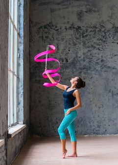 Linda mulher ginasta dançando com fita rosa