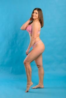 Linda mulher gorda sexy em estúdio. retrato de estúdio feminino, lingerie em um fundo azul