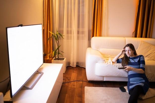 Linda mulher grávida assistindo televisão em seu apartamento moderno
