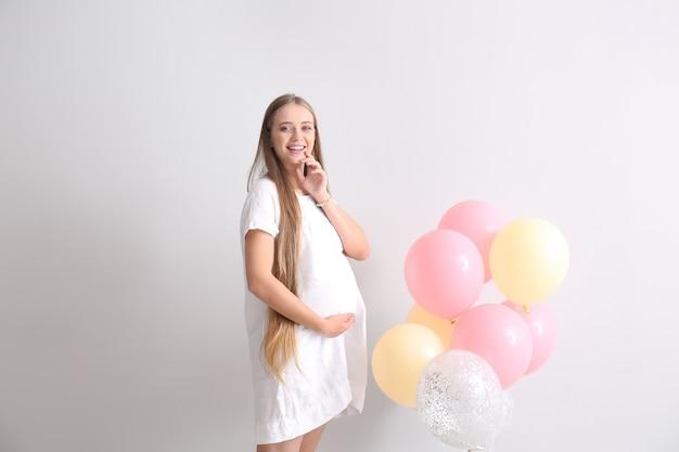 Linda mulher grávida com balões de ar em fundo branco