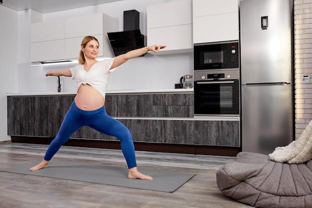 Linda mulher grávida com barriga grande fazendo exercícios de ginástica para alongamento com prazer