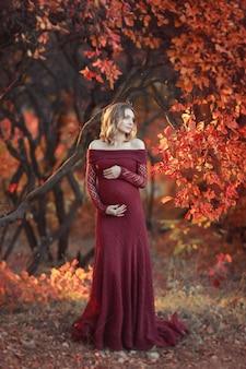 Linda mulher grávida com cabelos loiros em vestido vermelho longo e colar brilhante está de pé na floresta, sorrindo gentilmente para a câmera, cabelos loiros encaracolados flutuando ao vento. foto de arte de outono.