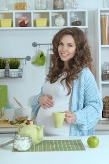 Linda mulher grávida com chá na cozinha