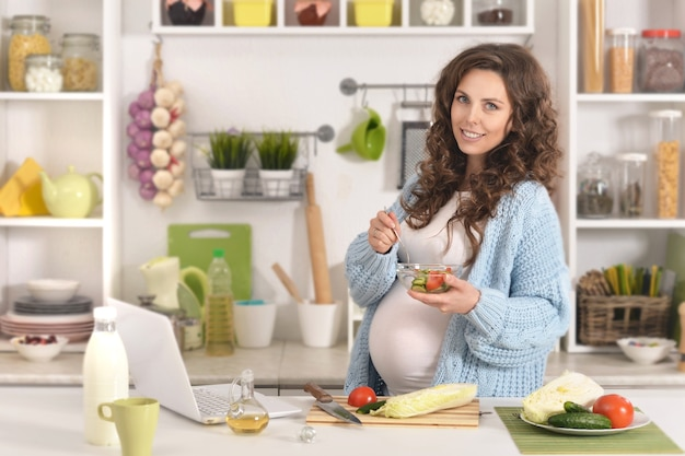 Linda mulher grávida com comida na cozinha