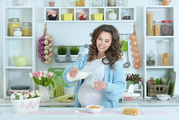 Linda mulher grávida com leite na cozinha