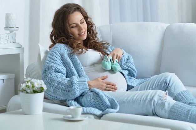 Linda mulher grávida com longos cabelos escuros e sapatos de bebê