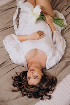 Linda mulher grávida com roupas brancas vista de cima cuidados de saúde