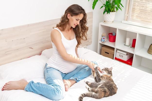 Linda mulher grávida de cabelos compridos sentada no sofá interno e brincando com um gato