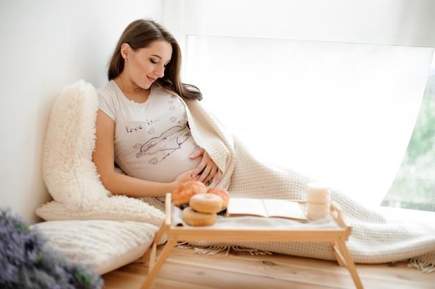 Linda mulher grávida deitada em um cobertor na cama branca