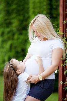 Linda mulher grávida e filha. menina bonitinha abraçando sua mãe grávida na natureza de verão.
