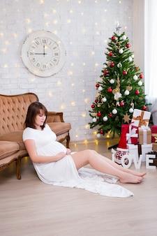 Linda mulher grávida em um quarto decorado com luzes de sofá vintage de árvore de natal e presentes