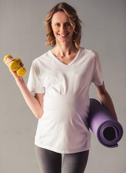 Linda mulher grávida está segurando halteres.