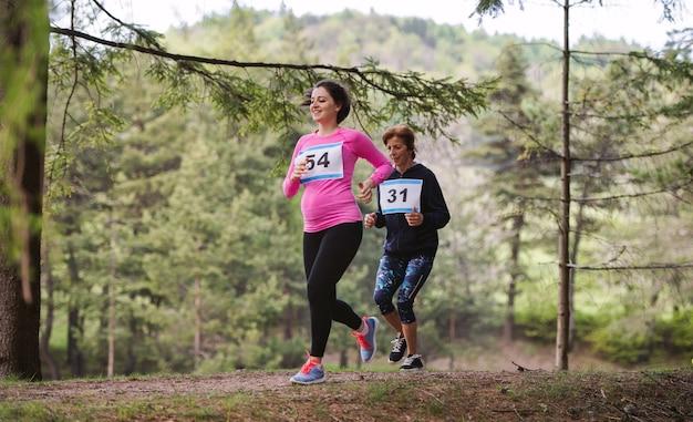 Linda mulher grávida executando uma competição de corrida na natureza.