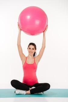 Linda mulher grávida fazendo exercícios com fitball