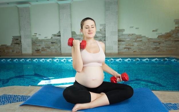 Linda mulher grávida fazendo exercícios com halteres perto da piscina