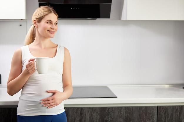 Linda mulher grávida feliz bebendo chá ou café na cozinha em casa pela manhã