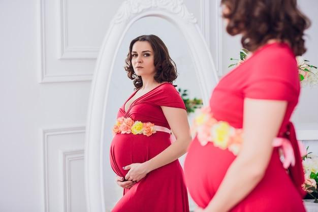 Linda mulher grávida olhando no espelho na sala de luz