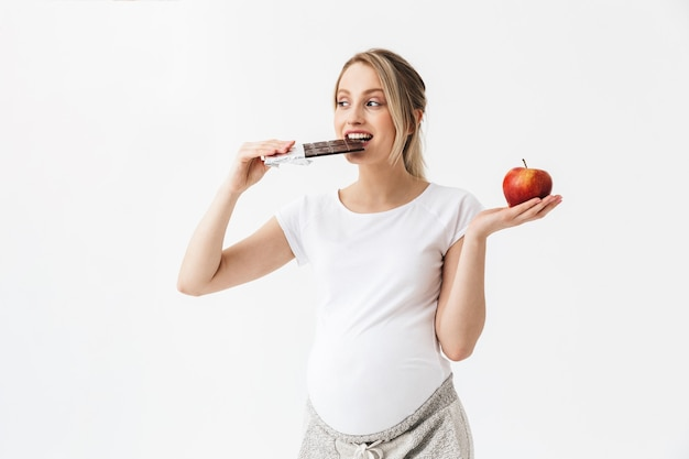 Linda mulher grávida segurando uma barra de chocolate e uma maçã vermelha isolada sobre um fundo branco