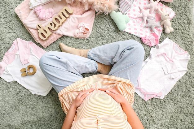 Linda mulher grávida sentada no chão com roupas de bebê, vista de cima