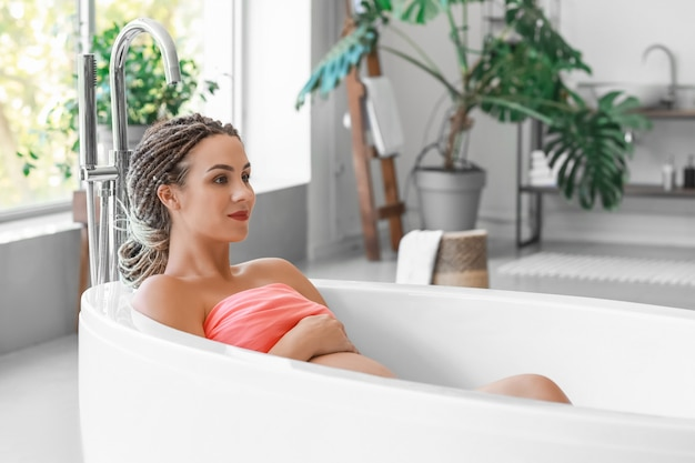 Linda mulher grávida tomando banho em casa