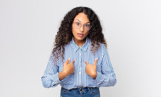 Linda mulher hispânica apontando para si mesma com um olhar confuso e questionador, chocada e surpresa por ser escolhida