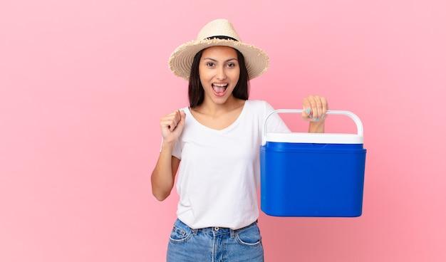 Linda mulher hispânica chocada, rindo, comemorando o sucesso e segurando uma geladeira portátil