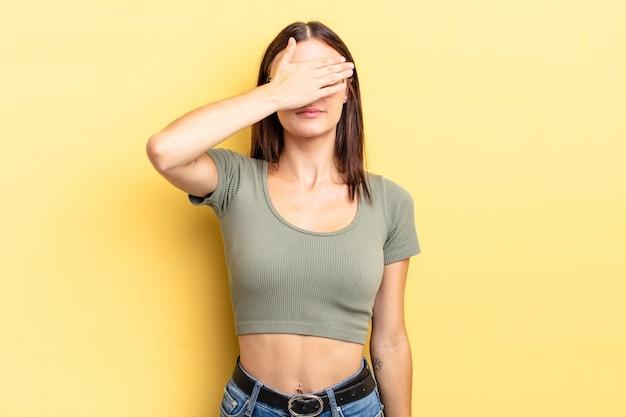 Linda mulher hispânica cobrindo os olhos com uma das mãos, sentindo-se assustada ou ansiosa, imaginando ou esperando cegamente por uma surpresa