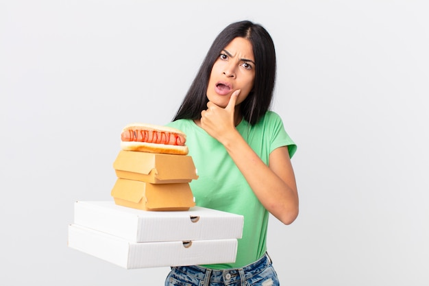 Linda mulher hispânica com a boca e os olhos bem abertos, a mão no queixo e segurando caixas de fast food