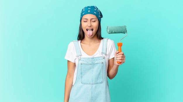 Linda mulher hispânica com atitude alegre e rebelde, brincando e mostrando a língua. conceito de pintura de casa