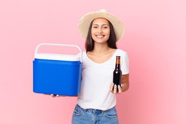 Linda mulher hispânica com um freezer portátil e uma cerveja