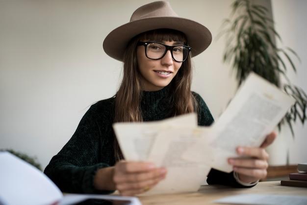 Linda mulher hispânica em elegantes óculos e chapéu trabalhando em casa
