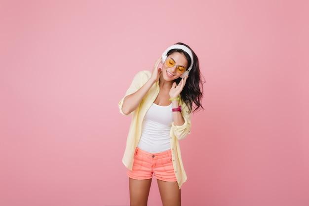 Linda mulher hispânica em relógio de pulso da moda ouvindo música com os olhos fechados. retrato interno da incrível modelo feminina latina em shorts rosa curtindo a música