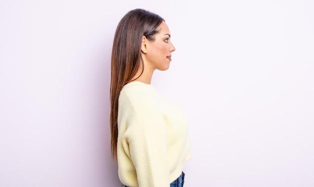 Linda mulher hispânica em vista de perfil olhando para copiar o espaço à frente, pensando, imaginando ou sonhando acordada