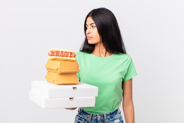 Linda mulher hispânica em vista de perfil pensando, imaginando ou sonhando acordada e segurando caixas de fast food para viagem