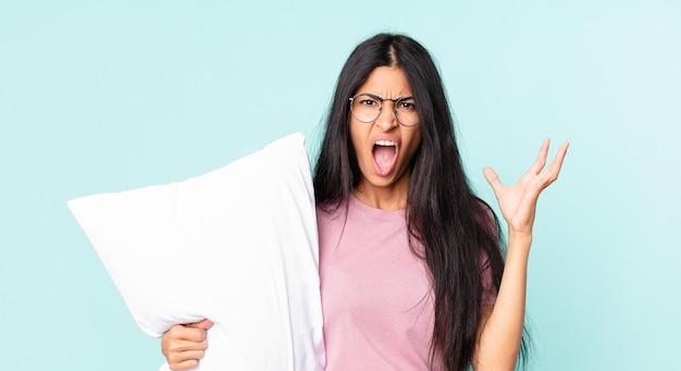 Linda mulher hispânica gritando com as mãos para o alto e usando pijama com um travesseiro