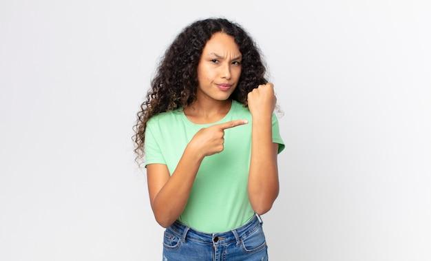 Linda mulher hispânica, impaciente e zangada, apontando para o relógio, pedindo pontualidade, quer ser pontual
