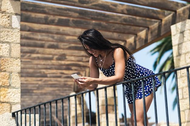 Linda mulher hispânica no vestido azul, apoiando-se na cerca enquanto estiver usando um telefone celular