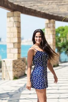 Linda mulher hispânica no vestido azul em pé ao ar livre enquanto olha para a câmera