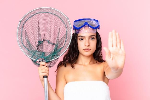 Linda mulher hispânica olhando séria mostrando a palma da mão aberta fazendo gesto de pare com óculos e rede de pesca