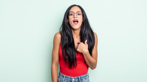 Linda mulher hispânica parecendo chocada e surpresa com a boca bem aberta, apontando para si mesma