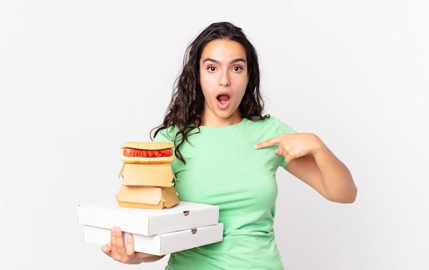 Linda mulher hispânica parecendo chocada e surpresa com a boca escancarada, apontando para si mesma e segurando caixas de comida rápida