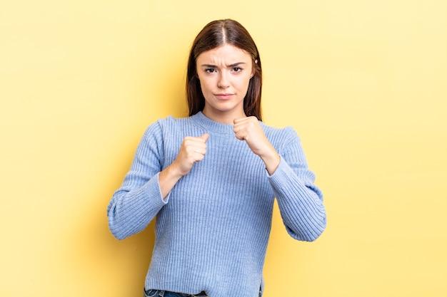 Linda mulher hispânica, parecendo confiante, irritada, forte e agressiva, com punhos prontos para lutar em posição de boxe
