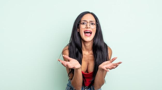 Linda mulher hispânica parecendo desesperada e frustrada, estressada, infeliz e irritada, gritando e gritando