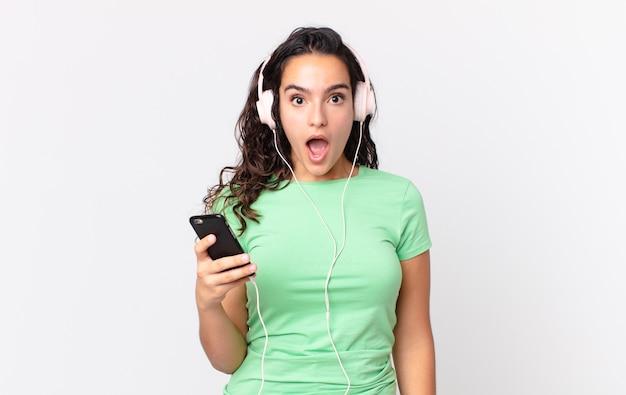 Linda mulher hispânica parecendo muito chocada ou surpresa com fones de ouvido e um smartphone