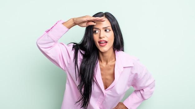 Linda mulher hispânica parecendo perplexa e atônita, com a mão na testa olhando para longe, observando ou procurando