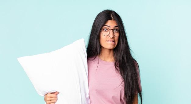 Linda mulher hispânica parecendo perplexa e confusa, usando pijama com um travesseiro