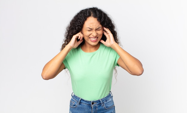 Linda mulher hispânica parecendo zangada, estressada e irritada, cobrindo os ouvidos de um barulho, som ou música alta ensurdecedores