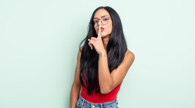 Linda mulher hispânica pedindo silêncio e sossego, gesticulando com o dedo na frente da boca, dizendo shh ou guardando segredo