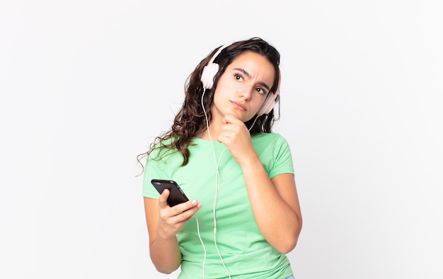 Linda mulher hispânica pensando, se sentindo em dúvida e confusa com fones de ouvido e um smartphone