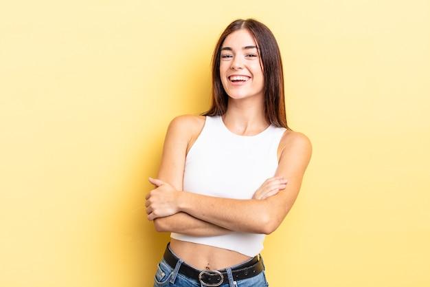 Linda mulher hispânica rindo alegremente com os braços cruzados, numa pose relaxada, positiva e satisfeita